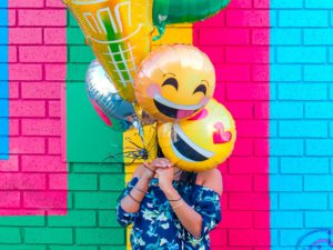 Woman with balloons shaped like emojis